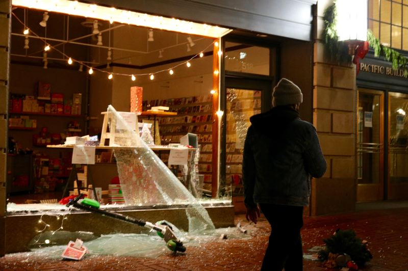 PMG PHOTO: ZANE SPARLING - A man walks past the busted-out storefront of Ecru Modern Stationers in downtown Portland early in the morning of Jan. 1.