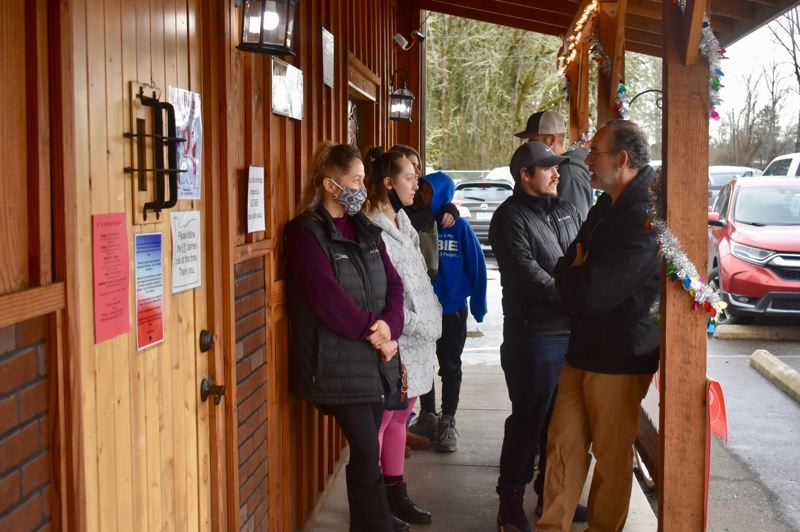 PMG PHOTO: EMILY LINDSTRAND   - Customers wait outside of Eagle Creek Saloon on Friday, Jan. 1.