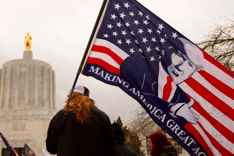 PMG PHOTO: ZANE SPARLING - A person holds a flag of President Trump at the Oregon state Capitol on Jan. 1.