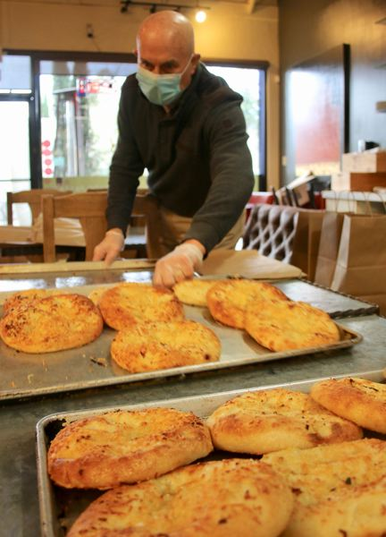Alan Newman, who owns Nicoletta's Table with his wife, Shari, preps loaves of focaccia bread to be ready for delivery to local families.