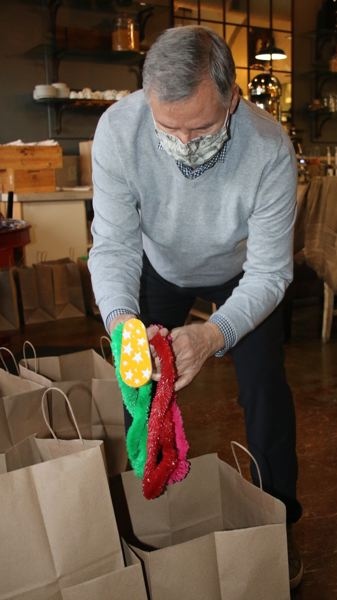 Malcolm Mathes fills food bags with New Year's party favors. He also helped to coordinate Lake Oswego Rotary Club members to help with the delivery of the meals to local families.
