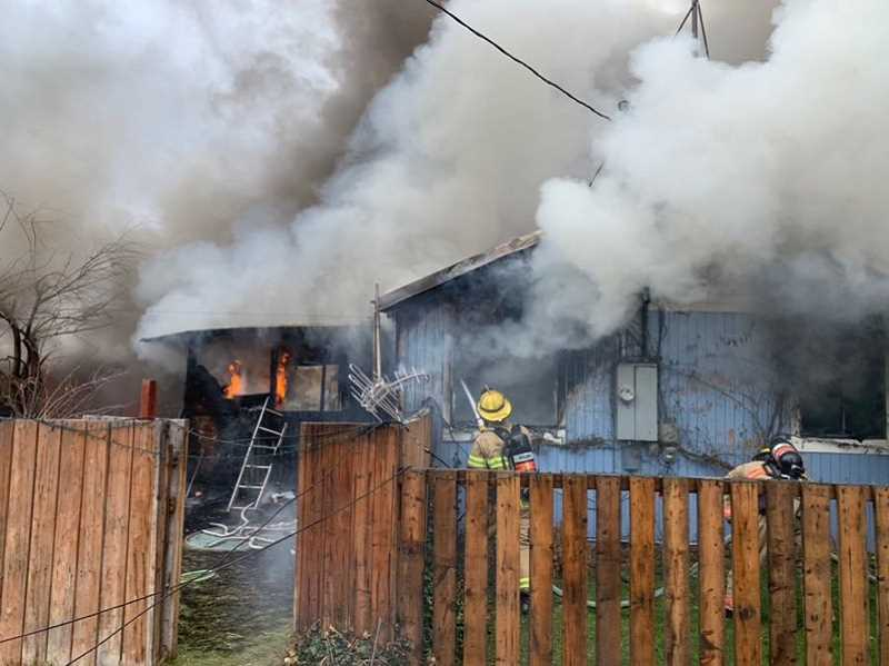 CROOK COUNTY FIRE AND RESCUE - Crook County firefighters work to contain a house fire that broke out late Saturday morning in southeast Prineville.
