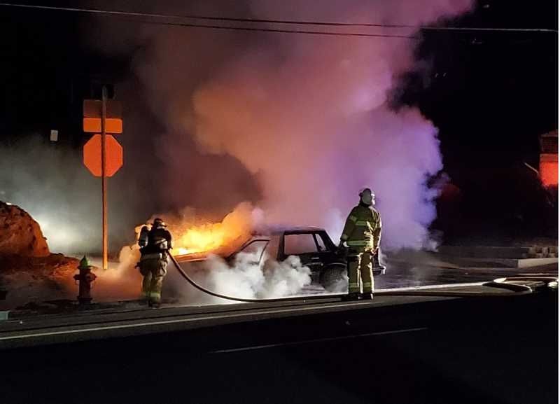PHOTO SUBMITTED BY KURT OCKER - Jefferson County Fire District crews work to extinguish a car fire at Fifth and Snook streets in Madras Sunday evening.