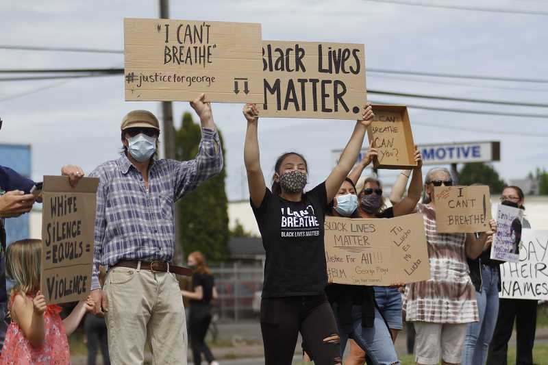 PMG PHOTO: WADE EVANSON - Demonstrators hold up signs beneath the giant flagpole in Forest Grove this past summer in support of the Black Lives Matter movement. Forest Grove residents continue to rally for change in the wake of two separate incidents in recent months involving Forest Grove police officers.