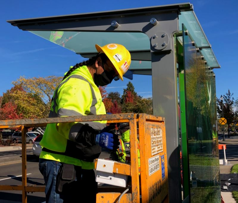 COURTESY TRIMET - A worker at a bus stop station shelter prototype installed at Northwest Division Street and Eastman Parkway