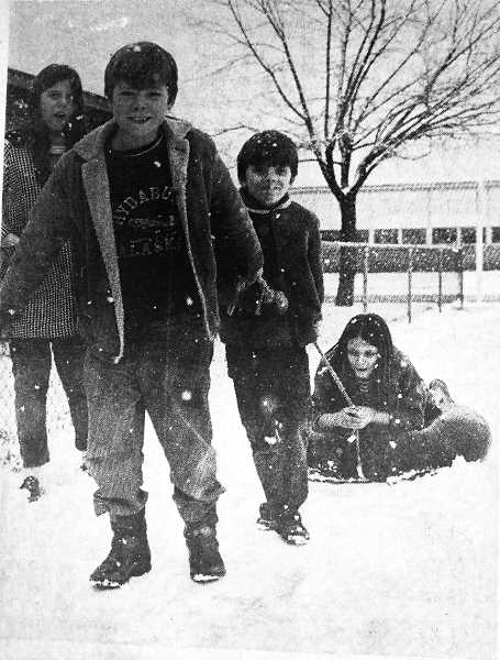 CENTRAL OREGONIAN - January 7, 1971: Start with a new snowfall, an innertube, piece of rope; add four kids and a dog, and you'll end up with a good time. Tim Walburn, 10, and his brother Lyndon, 8, were busy pulling sister Becky, 11, as Vicki, 12, skated alongside. The four were enjoying the snow Dec. 29 as it fell near the high school. Prancer, their dog, also joined them in their fun during Christmas vacation.