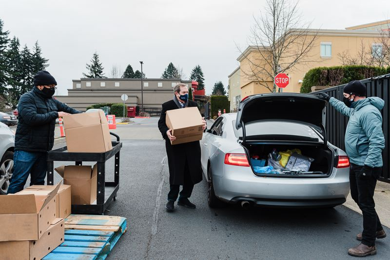COURTESY PHOTO: HARSCH INVESTMENT PROPERTIES - Jordan Schnitzer (black overcoat) loads a box of food into a waiting car Dec. 29 at Gresham Station. Schnitzer is president of Harsch Investment Properties, whch owns Gresham Station,