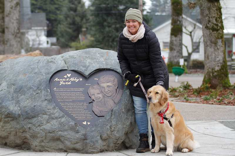 PMG PHOTO: WADE EVANSON - Susan Dieter-Robinson poses for a photo next to the plaque in Abby and Abby's Yard honoring her daughters, who died in 2013.