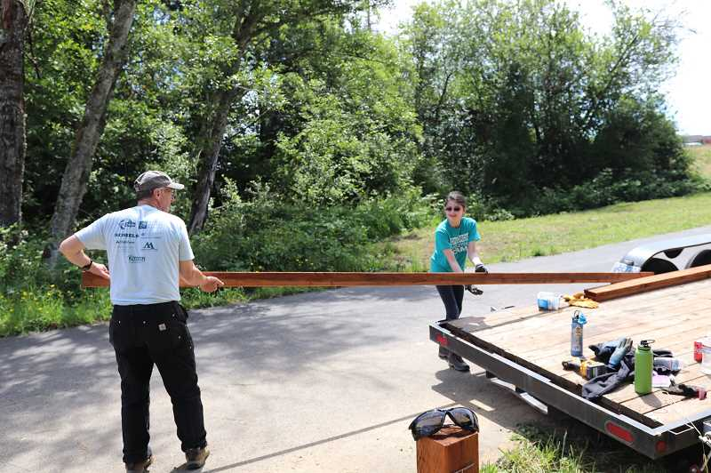 COURTESY OF AMANDA BECKER - Scott Winegar and Elisabeth Becker lift wood planks from a trailer to build a pedestrian bridge for Columbia County Christian School students.