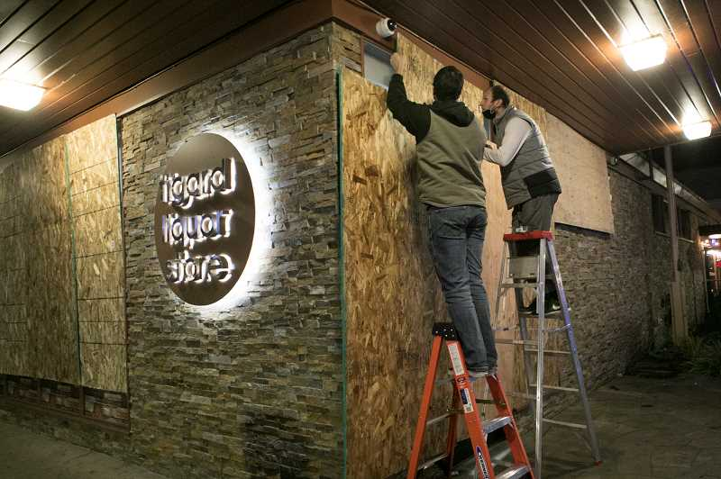 PMG PHOTO: JAIME VALDEZ - Brendan Saunders (right) of Tigard Spirits gets help covering the facade of his business in plywood to prevent damage during a protest over a fatal shooting by Tigard police.