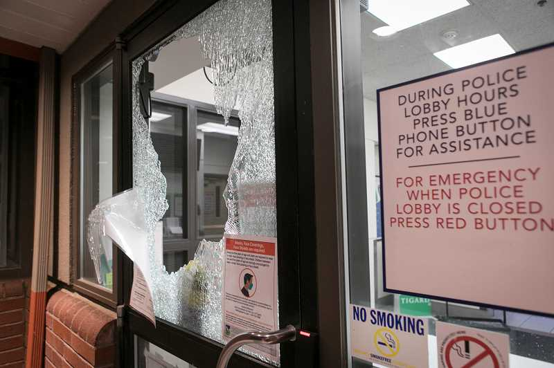 PMG PHOTO: JAIME VALDEZ - A window at the Tigard Police Department headquarters is smashed out by rioters following a direct action march targeting the police building Thursday, Jan. 7.