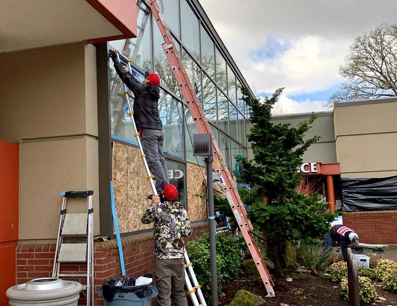 PMG PHOTO: JAIME VALDEZ - Work crews replace glass on Tigard City Hall windows Friday after they were smashed during a protest the night before. Protesters marched to the Tigard Police Station, behind tree, to protest the killing of Jacob MacDuff, 26, by police. In all, the front door of the police station was smashed in and a total of 20 windows were broken in the police facility and Tigard City Hall.