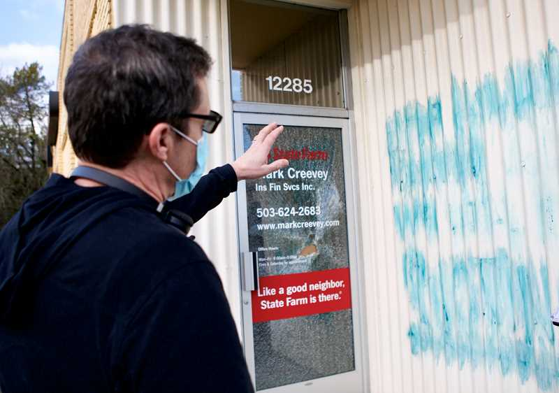 PMG PHOTO: JAIME VALDEZ - State Farm Agent Mark Creevey explains the graffiti that was on the outside of his office following protests through the city Thursday night. Creevey's front door was also smashed in.