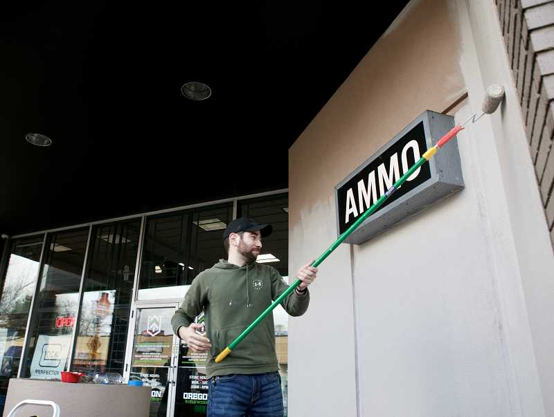PMG PHOTO: JAIME VALDEZ - Tony Perrizo, an employee with Oregon Rifleworks on Tigard's Main Street, paints over graffiti demonstrators sprayed on the outside of the building Thursday night.