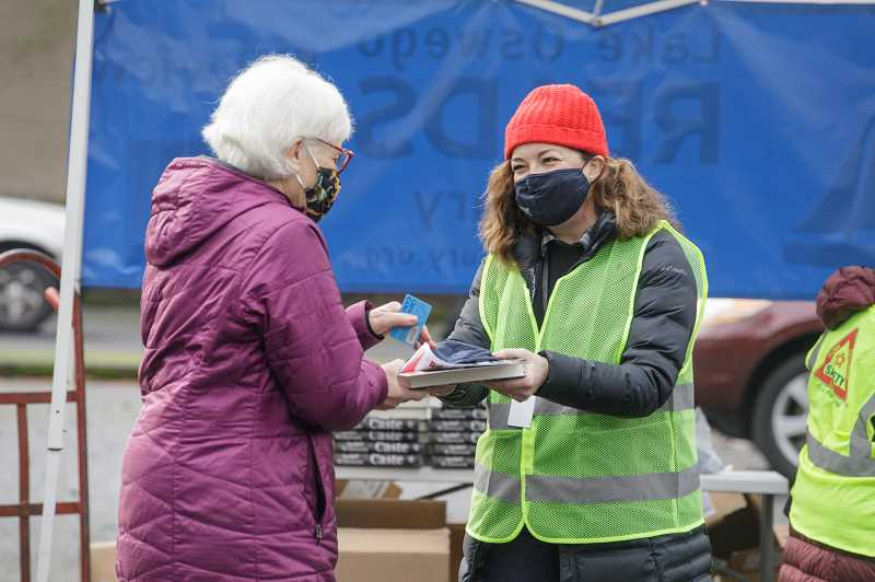 PMG PHOTO: JONATHAN HOUSE - Lake Oswego Library's Nancy Niland helps hand out copies of 'Caste' during the LO Reads book giveaway on Thursday, Jan. 7.