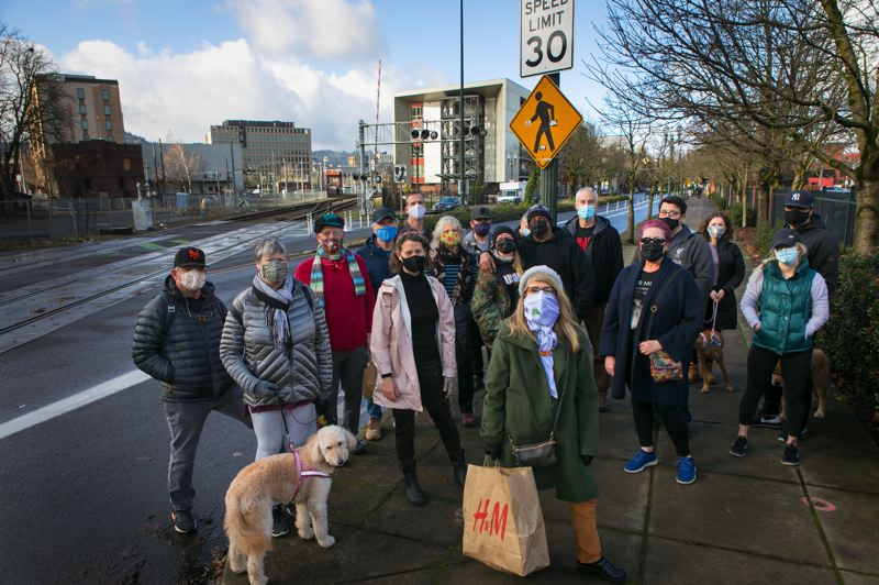 PMG PHOTO: JAIME VALDEZ - More than a dozen residents living near the Northwest Naito Parkway railroad crossing recently met to complain about the train horns. They included Lawrence Freeman, standing in the back row with a blue mask.