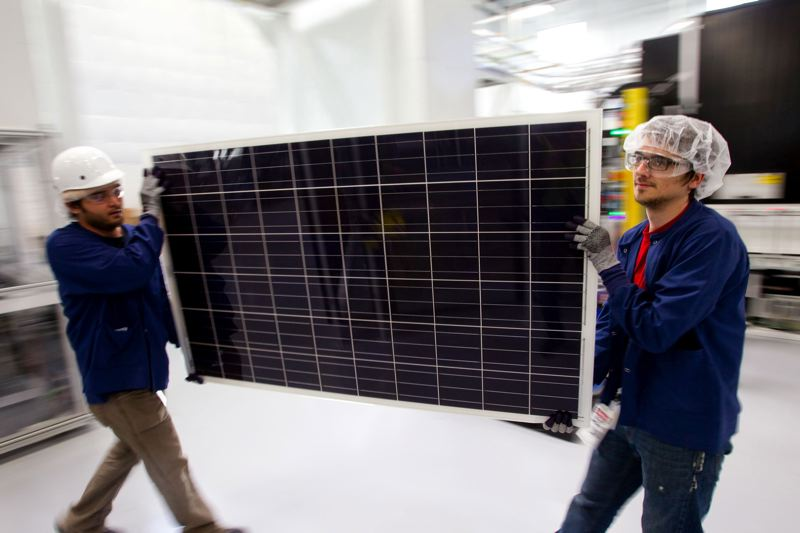 PMG FILE PHOTO - In 2010, Sam Taylor (right) and Graig Nielson are pictured carrying a solar panel through SolarWorld Industries America's large-scale production facility in Hillsboro, which employed hundreds. SolarWorld moved its operations to Hillsboro in 2008.