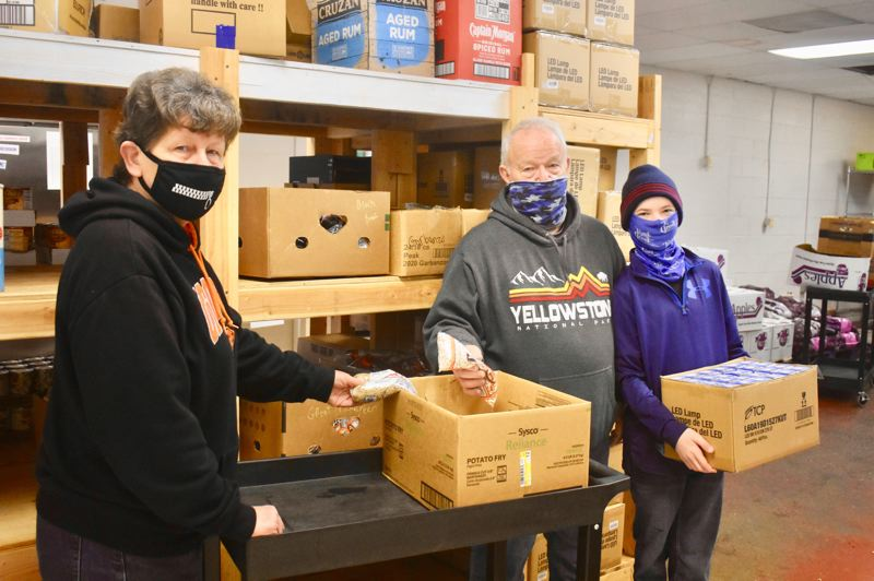 PMG PHOTO: EMILY LINDSTRAND - Debbie Mullins (left to right), Dave Mullins and Bernie Bast are regular volunteers at the Estacada Area Food Bank.