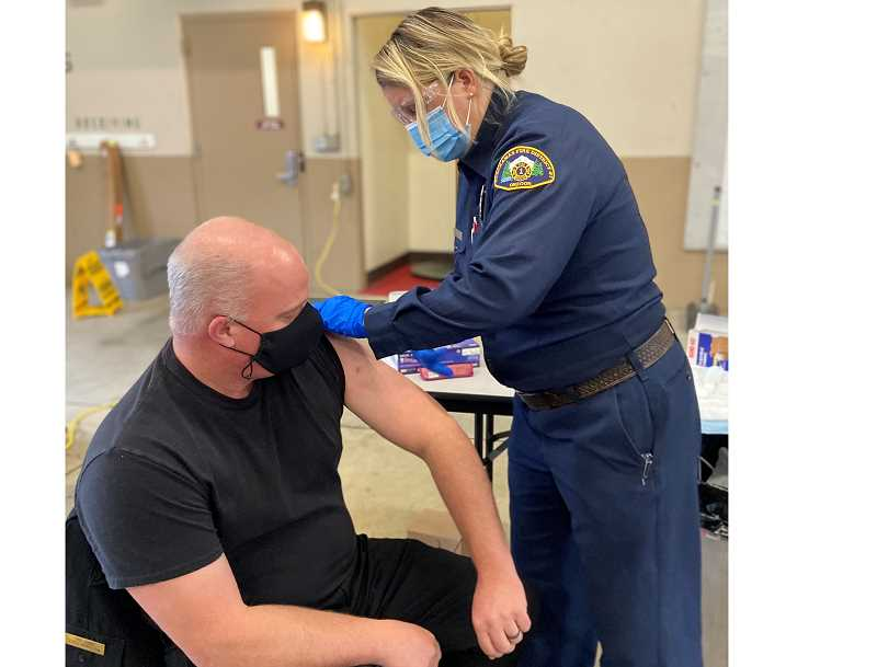 COURTESY PHOTO: CLACKAMAS FIRE - Community Paramedic Amy Jo Cook administers the first dose of COVID-19 vaccine to Fire Chief Fred Charlton.
