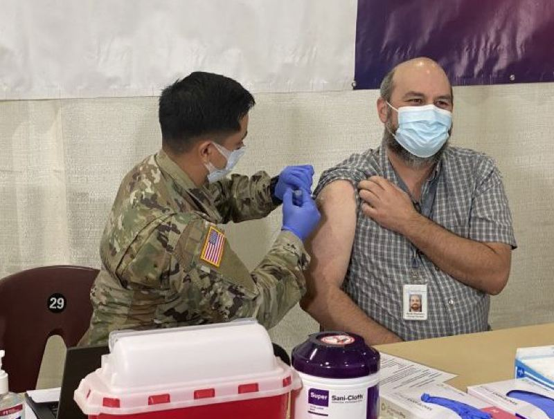COURTESY: OREGON GOV. KATE BROWN OFFICE - A member of the Oregon National Guard gives the COVID vaccine to a man at the Oregon State Fairgrounds in Salem, on Jan. 13.