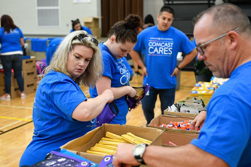 PMG FILE PHOTO - Comcast employees fill backpacks with school supplies at Lincoln Street Elementary School in Hillsboro in 2019.