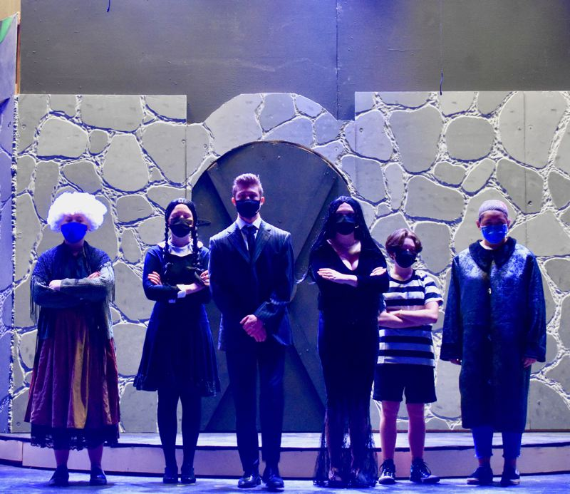 PMG PHOTO: EMILY LINDSTRAND - Grandma (Breanna Ruiz), Wednesday (Lizzie Smith), Gomez (Andrew Riedel), Morticia (Irelynd ONeill), Pugsley (Ava Shibahara) and Uncle Fester (Ayla Zallee) gather at the beginning of Estacada High Schools production of The Addams Family.