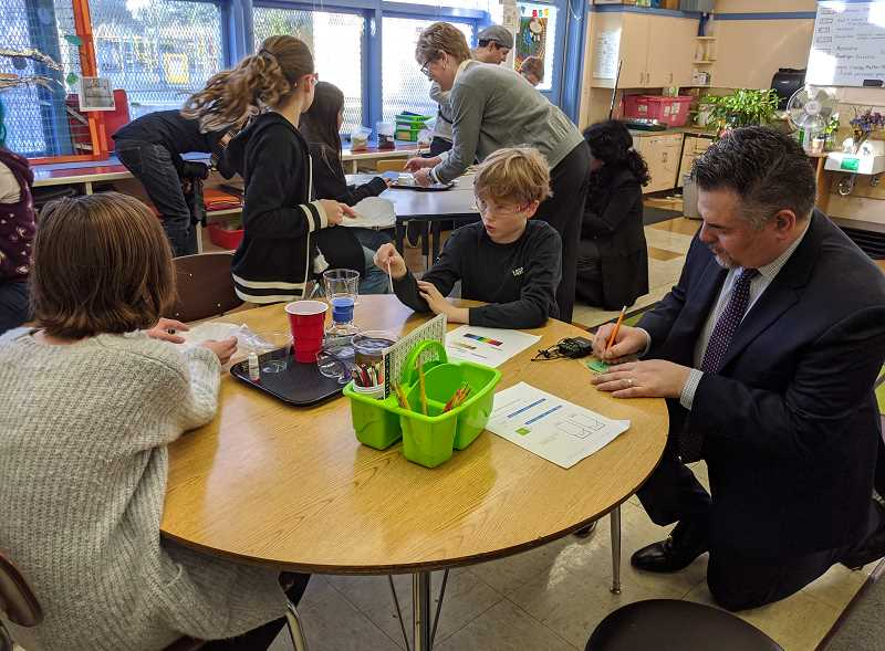 PMG FILE PHOTO - Portland Public Schools Superintendent Guadalupe Guerrero (right) kneels at a table alongside students at Bridger K-8 school during a January 2020 special activity with PGE staff. Distance learning has led to a lower percentage of students of color attending school regularly.