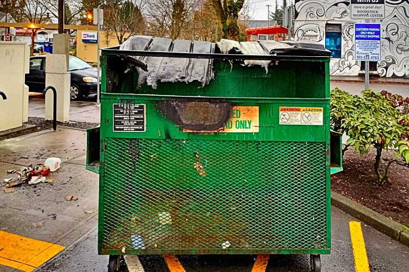 COURTESY OF GENE DIERINGER - In mid-December, an arsonist set fire to this cardboard recycling bin - here shown burning behind a Woodstock Boulevard business office.