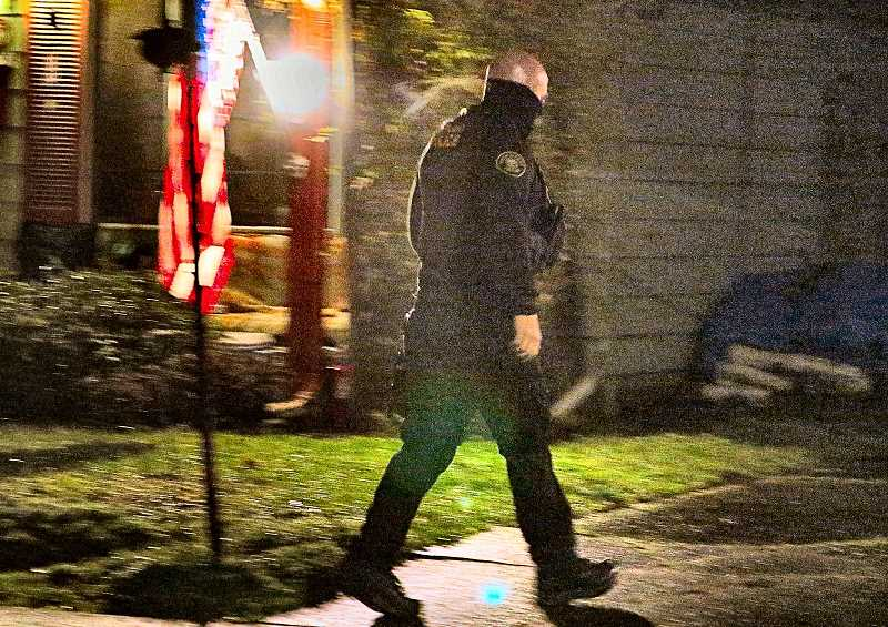 DAVID F. ASHTON - An East Precinct officer searches for evidence, after a rare home invasion robbery on S.E. Woodstock Boulevard near 74th.