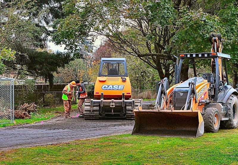 DAVID F. ASHTON - Working in Flavel Park, construction crewmembers checked their work against the plans, as they got ready to pave the multi-use path - part of the Springwater Connector Neighborhood Greenway project still underway in Brentwood-Darlington.