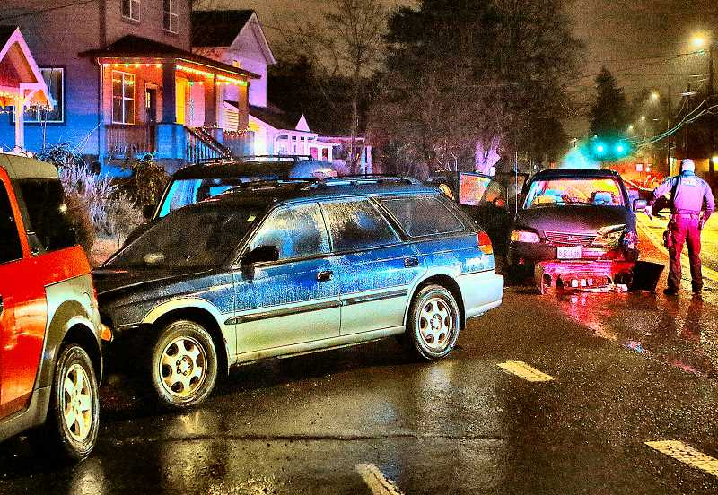DAVID F. ASHTON - An East Precinct officer examined the damage after a head-on crash in the rain on Woodstock Boulevards notorious curve at S.E. 69th.