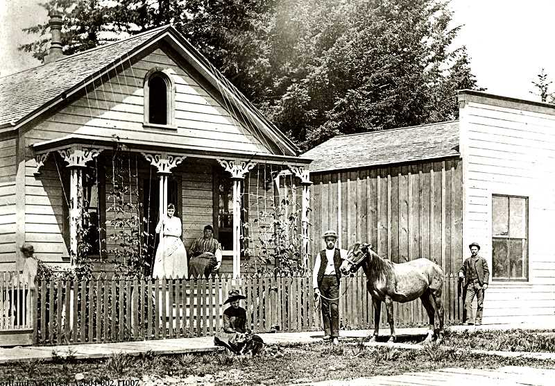 COURTESY OF CITY OF PORTLAND ARCHIVES - Heres one of the earliest barbershops on Umatilla Street in the early 1900s; its  proprietor is unidentified. It might have been where C.A. Williams lived, or  perhaps a reader might be able to identify the house. In those days the streets of Sellwood were unpaved, and merchants often lived next door to their place of business.