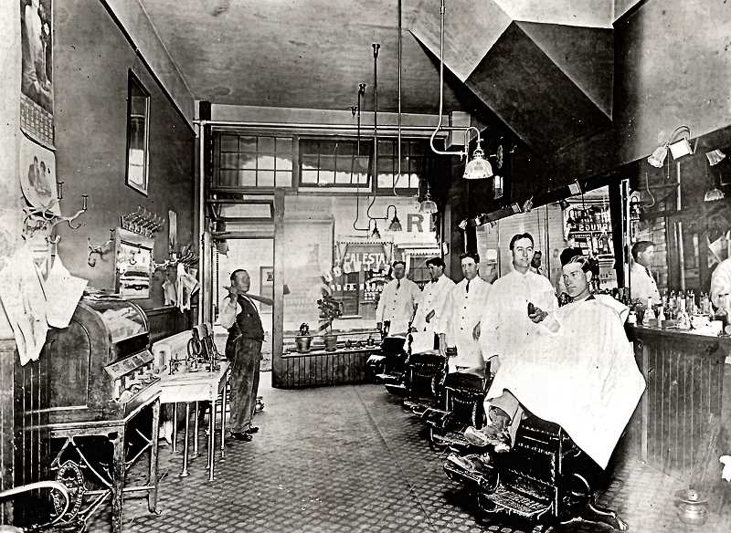 COURTESY OF HARRY MAY AND SMILE HISTORY COMMITTEE - The Sellwood Barbershop on 13th Avenue, often called Ed Trites Barbershop, was one of the premiere shops on the entire east side of Portland. The four barbers shown, from left, are Jim Roberts, Bert Wescott, Ed Trite, and Martin Larsen - and a barbers assistant stands nearby to clean up after the barbers. This photo was probably taken in about 1930, when Jacob Schick patented the electric razor shown in the hand of the barber on the end, with a customer in the chair.