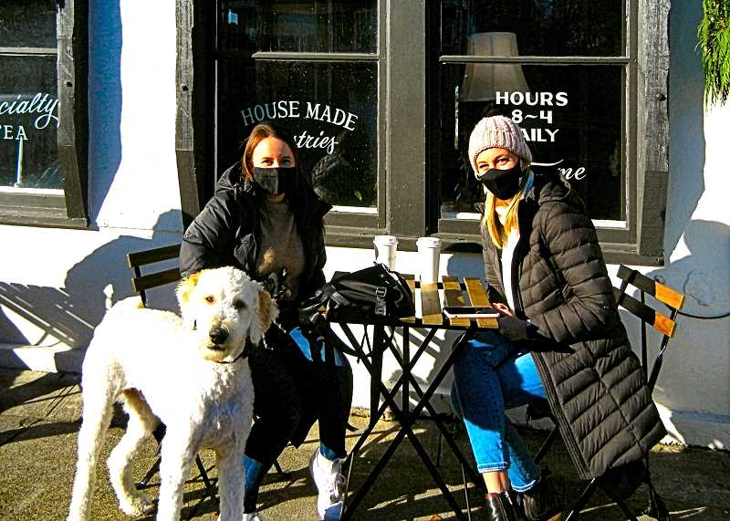 ELIZABETH USSHER GROFF - Sitting outside, drinking their coffee at Keeper Coffee, are customers Abby from Gresham, and Danielle Stipe from Canby. Henry the Golden Doodle is also enjoying the sunshine.