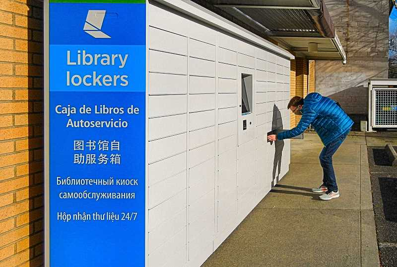 ELIZABETH USSHER GROFDF - Woodstock resident Ned Holbrook is shown picking up a book from one of the 90 self-service hold lockers outdoors off the Woodstock Library parking lot. He entered his library card number on the screen, and his locker door popped open with his book inside.
