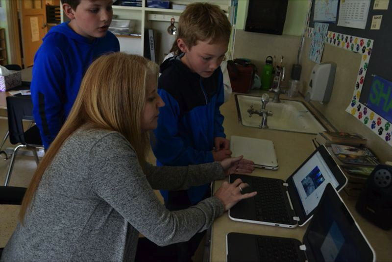 PMG FILE PHOTO: BRITTANY ALLEN - Jeannine Hokanson helps a student with their Chromebook in a classroom pre-pandemic.