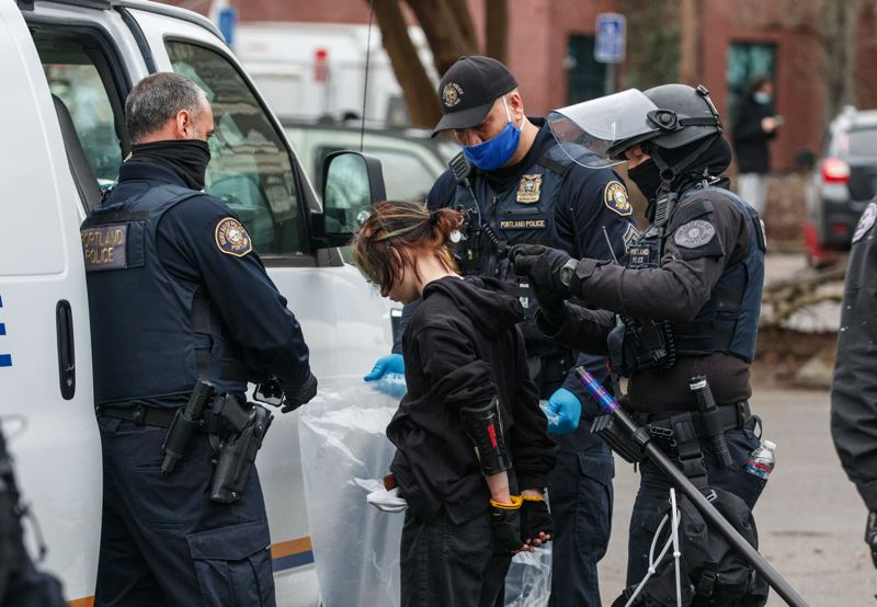 PMG PHOTO: JONATHAN HOUSE - Portland Police take a person into custody during a protest on Jan. 20.