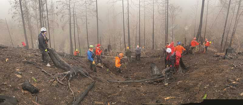 COURTESY PHOTO: CCSO - Rescue crews descend the side of a mountain during the investigation of skeletal remains southeast of Molalla.