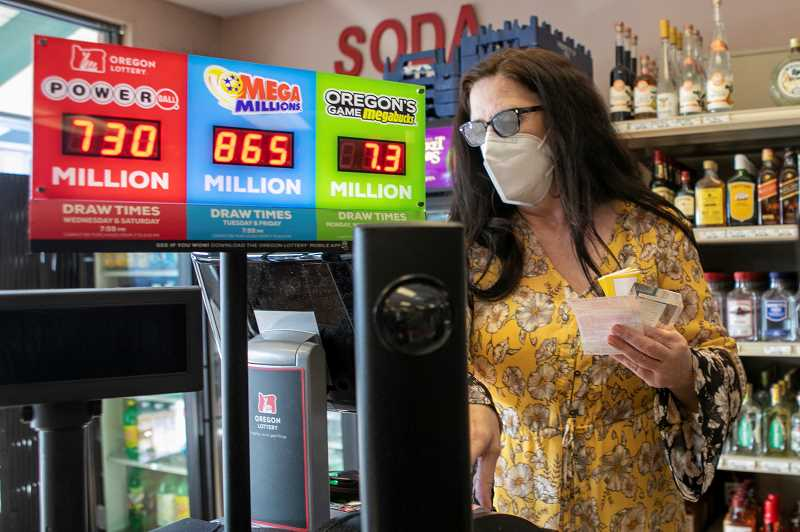 PMG PHOTO: JAIME VALDEZ - Sherri Daniels prints out lottery tickets for a customer at her business, the King City Liquor store. The store recently sold a winning $1 million Oregon Lottery Mega Millions game ticket to a Tigard couple.