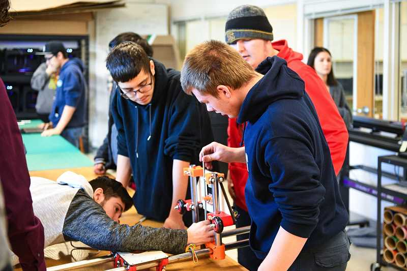 PMG PHOTO: CHRISTOPHER OERTELL - Students work on assembling a CNC router so they can build a small jetboat as part of their mechatronics class at Forest Grove High School. Forest Grove School District announced last week their plans to reopen schools in April.