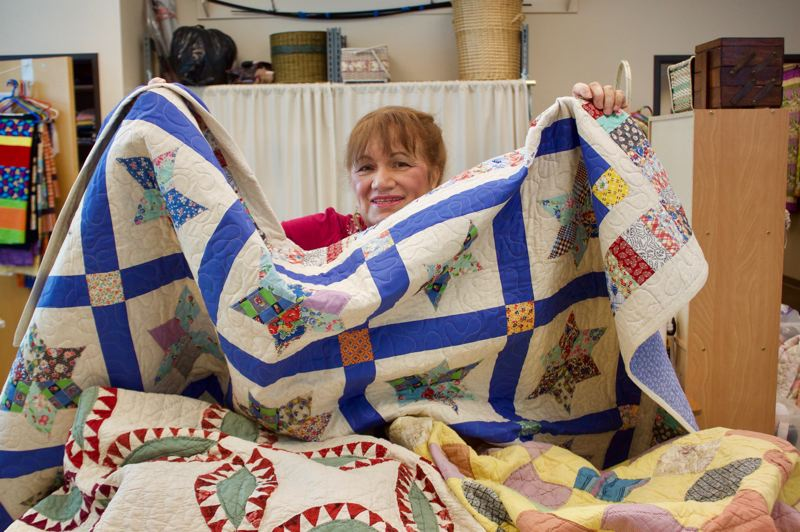 PMG FILE PHOTO - Midge Nasiatka shows off one of the beautiful quilts made and sold by the Gresham Senior Center.