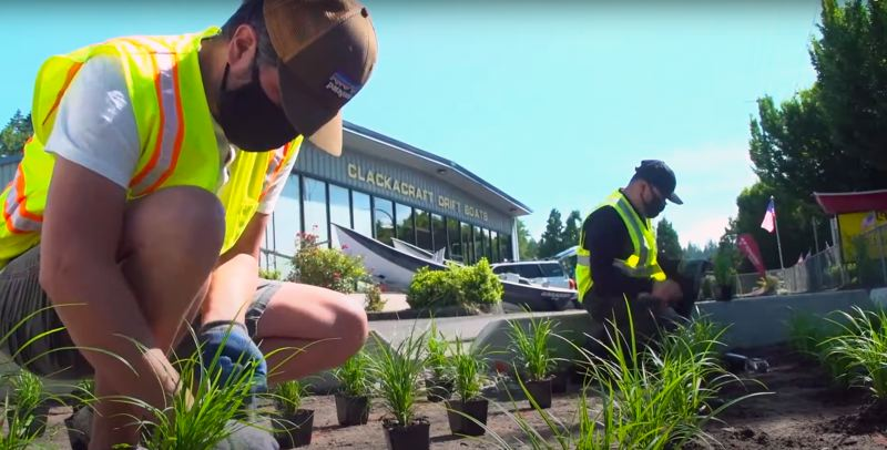 PHOTO COURTESY OF CLACKAMAS WATER ENVIRONMENT SERVICES - Employees with ClackaCraft Drift Boats completed a stewardship project last year in which they installed a rain garden at their headquarters off Highway 212.