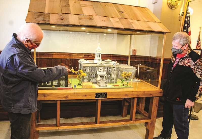 JASON CHANEY - Jim Brinkley (right), who built the display cabinet, and Tommy Sikes, cousin of Lonnie Sikes who built the building replicas, admire the new display.