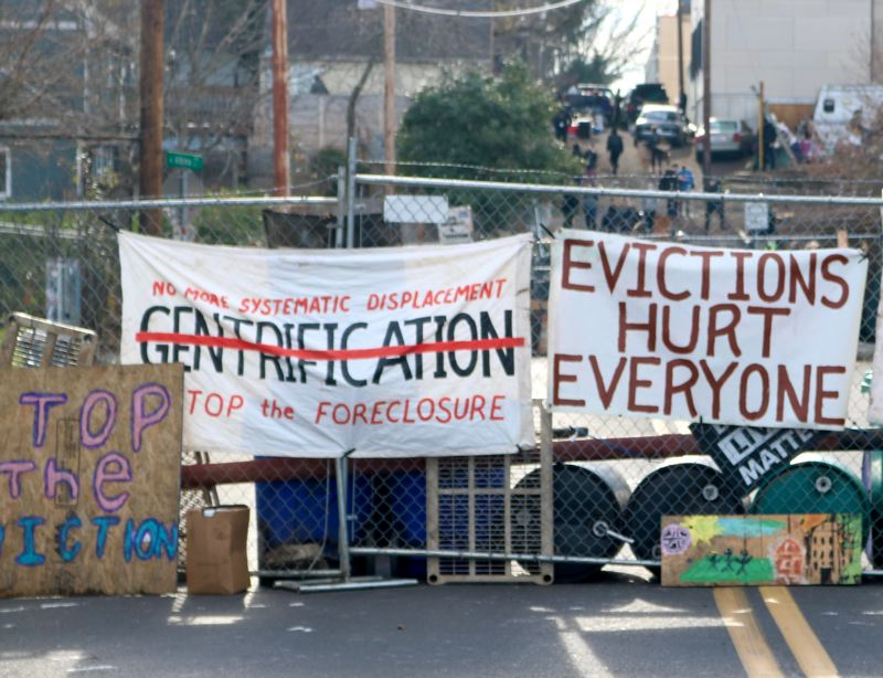 PMG PHOTO: ZANE SPARLING - Banners decrying evictions and gentrification were hung across street barricades during the Red House eviction defense in December.