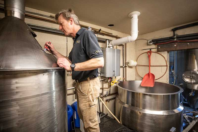 PMG FILE PHOTO - Binary Brewing head brewer Roger Wood checks the kettle level at their Scholls Ferry Road location in February of 2020.