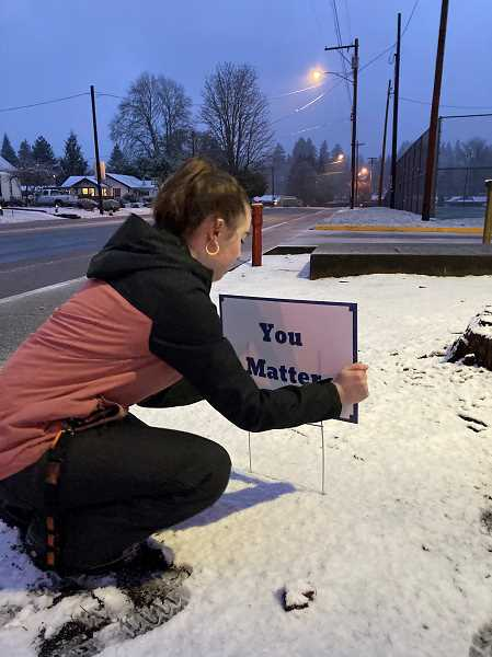 COURTESY PHOTO: KATE PATRICK - Kate Patrick installs a small sign reading 'You Matter' along a Scappoose street.