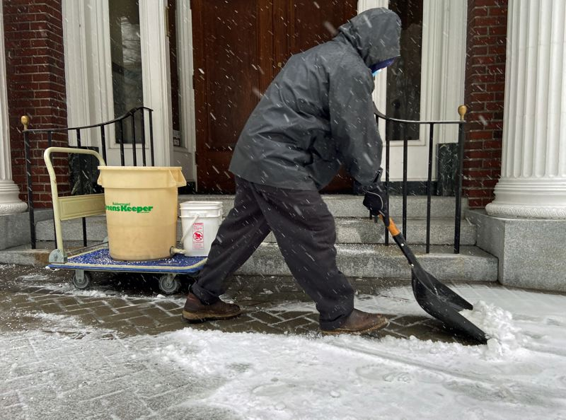 PMG PHOTO: DANA HAYNES - Carlos Alvarez shovels and sands a sidewalk at Southwest Salmon Street and Park Avenue early Friday, Feb. 12.