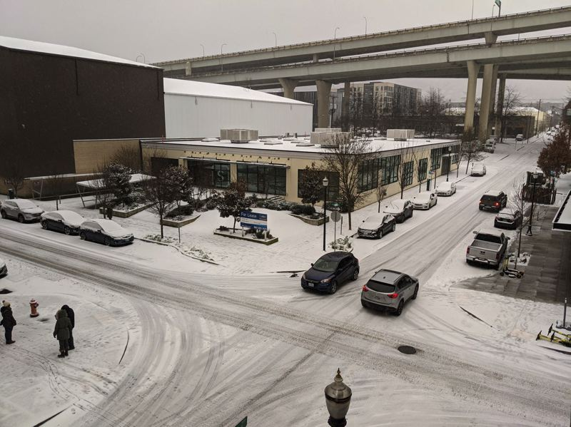 PMG: JOSEPH GALLIVAN - Snow began to settle Friday morning in Portland's Pearl District at Northwest 14th Ave and Quimby after snow ploughs had passed through.