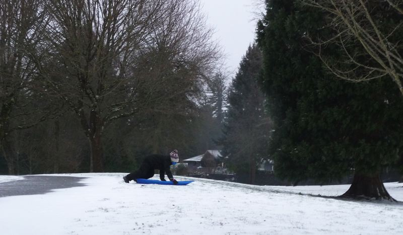 PMG PHOTO: TIFFANEY O'DELL - Jackson McCall, 7, gives his sled a push at Gresham's Bella Vista Park on Friday morning in the wind and freezing temperatures.