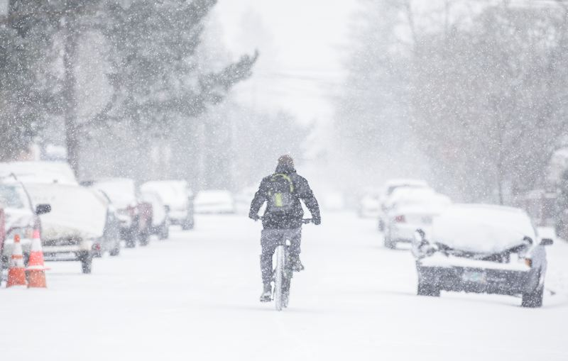 PMG PHOTO: JONATHAN HOUSE - A cyclist makes his way through the snow-covered streets of SE Portland.